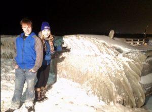 Casal posando ao lado de carro congelado
