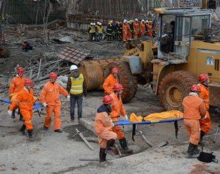 Equipe de resgate carrega o corpo de uma vítima retirado dentre escombros após o desabamento de parte da estrutura de uma torre de resfriamento de usina elétrica em construção em Fengcheng, na província de Jiangxi, na China (Foto: Reuters/Stringer)