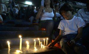 Criança acende velas para vítimas (Foto: RAUL ARBOLEDA / STR / AFP)
